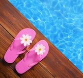 Concepto de vacaciones, flip flops a la piscina — Foto de Stock