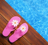 Holiday concept, flip flops a the pool — Photo
