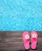 Holiday concept, flip flops a the pool — Stock Photo