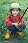 Smiling little boy holding fishing rod — Stock Photo
