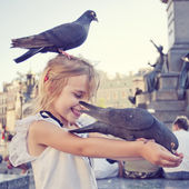 Smiling girl with pigeon on the head and the arms — Stock Photo