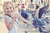 Smiling girl with pigeons on the arm — Stock Photo