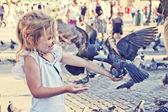 Smiling girl with pigeons on the hand — Stock Photo