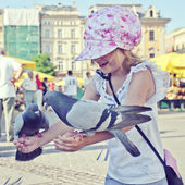 Smiling girl with pigeons on the hands — Stock Photo