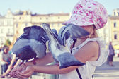 Little girl with pigeons on the arms — Stock Photo
