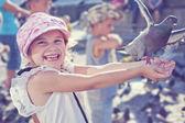 Smiling girl feeding pigeon — Stock Photo