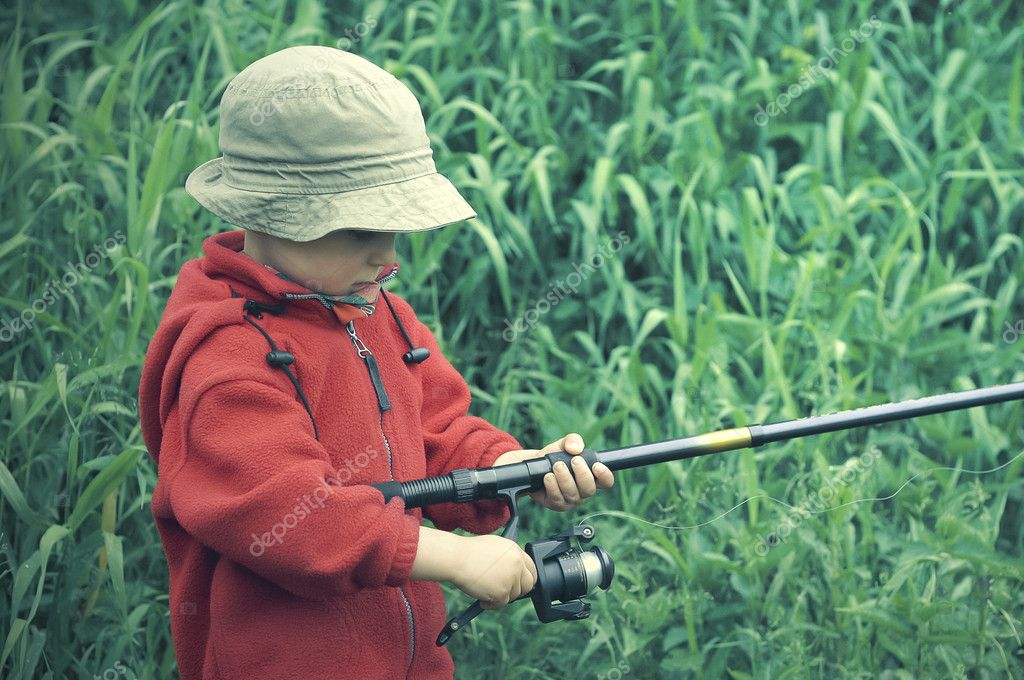 Little boy holding fishing rod stock photo przemekklos for Little kid fishing pole