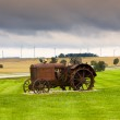 Old rusty tractor with wind turbines in the background. — Stock Photo #11794660