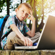 Thoughtful boy with laptop — Stock Photo