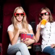 Two girls look three-dimensional cinema — Stock Photo