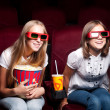 Two beautiful girls watching a movie at the cinema — Stock fotografie