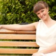 A beautiful woman is sitting on a park bench — Stock Photo #11022261