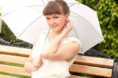 Beautiful young woman under white umbrella — Stock Photo