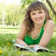 Woman in a park reading a magazine — Stock Photo