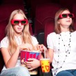 Two girls watching a movie at the cinema — Stock Photo