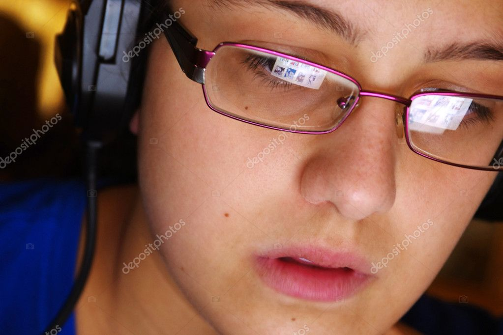 Hi-tech youth concept with a young girl using headphones and glasses reflecting her computer screen — Stock Photo #11520701