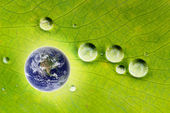 Nature conservation- glowing earth & water drops — Stock Photo