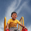 Happy smiling and handsome indian kid having fun playing in slid — Stock Photo #12223703