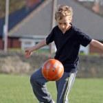 Teenage boy playing football — Stock Photo