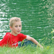 Royalty-Free Stock Photo: Teenage boy sat by a lake