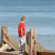 Teenage boy looking out the sea — Stock Photo