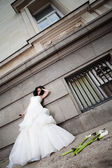 Frustrated bride leaning on wall — Stock Photo