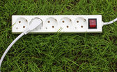 An power strip lying on the grass — Stock Photo