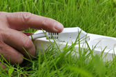 Power strip lying on the grass and hand — Stock Photo