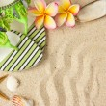 Green Sandals, seashells, starfish and frangipani on sand — Stock Photo