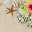 Sandals, seashells, and hibiscus on sand — Stock Photo