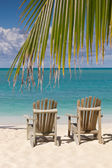 Beach chairs on white sand beach with blue sky and palm tree branch — Stock Photo