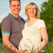 Pregnant couple in the park — Stockfoto
