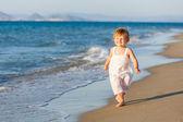 Little girl walking on the beach — Стоковое фото