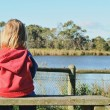 Stock Photo: Lonely girl on bench