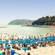 Crowded beach on the Ligurian Sea, Lerici , Italy with blue umbrellas — Stock Photo #11456716