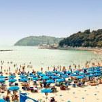 Crowded beach on the Ligurian Sea, Lerici , Italy with blue umbrellas — Stock Photo #11456716