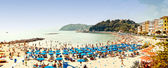 Crowded beach on the Ligurian Sea, Lerici , Italy with blue umbrellas — Stock Photo