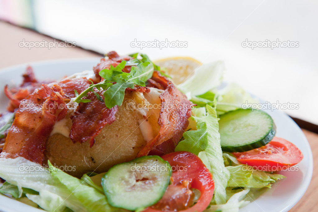 Jacket potato with sour cream and grated cheese on green salad — Stock Photo #11144743