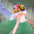Hand holding beautiful flower bouquet — Stock Photo