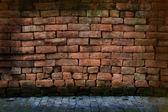 Vuile grunge rode stenen muur met bestrating — Stockfoto