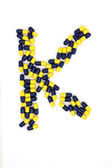 The letter K alphabet made of medical capsules — Stock Photo