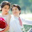 Stock Photo: Portrait of bride and groom making eye contact with rose bouquet