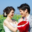 Portrait of bride and groom seeing each other on sunflower field - Stock Photo