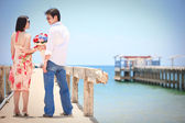 Couples make eye contact at pier on the beach — Stock Photo