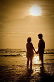 Romantic Scene of couples on the Beach with sunset — Stock Photo