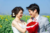 Portrait of bride and groom seeing each other on sunflower field — Stock Photo