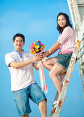 Couples holding beautiful flowers bouquet together on the beach — Stock Photo