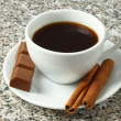 Cup of coffee with chocolate and cinnamon sticks — Stock Photo