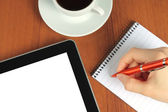 Touch screen device, notepad, writing hand and cup of coffee — Stock fotografie