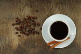 Cup of coffee with beans and cinnamon sticks — Stock Photo